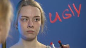 Verstoord tienermeisje die met lippenstiftwoord lelijk schrijven op spiegel, laag zelfrespect stock footage