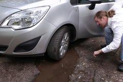 Verstoorde bestuurdersmens die voor auto op beschadigde auto letten van Stock Foto