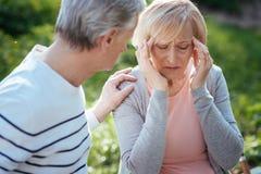 Verstoorde gepensioneerde die vreselijke pijn in het hoofd in openlucht voelen stock foto's
