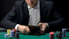 Verstoorde gokker die in lege portefeuille, verliezer bij casinolijst kijken, spelverslaving stock afbeeldingen