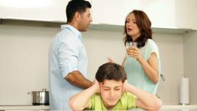 Verstoorde jongen die zijn oren behandelen terwijl zijn ouders vechten stock videobeelden