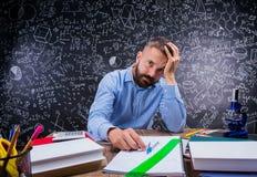 Verstoorde leraar bij bureau, schoollevering, die hoofd, bord houden royalty-vrije stock foto