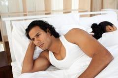 Verstoorde man in bedslaap afzonderlijk van een vrouw stock fotografie