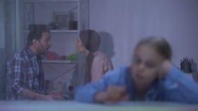Verstoorde meisjeszitting achter regenachtig venster, het luisteren oudersruzie, problemen stock footage