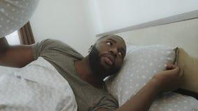 Verstoorde mens die in bed in ochtend liggen Afrikaans volwassen behandelend hoofd met hoofdkussen stock footage