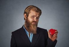Verstoorde mens die en rode grote hartvorm bevinden zich houden royalty-vrije stock foto's