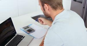 Verstoorde mens die zijn boekhouding met laptop doen stock footage