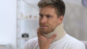 Verstoorde mens in schuim cervicale kraag die aan halsongemak lijden, rehabilitatie stock video