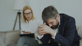 Verstoorde schreeuwende zakenmanpatiënt die zijn hoofd houden door handen die aan zijn psychoanaliticus in haar bureau spreken stock footage