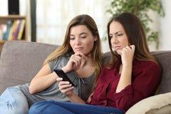 Verstoorde vrienden die op online inhoud in een slimme telefoon letten royalty-vrije stock foto