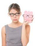 Verstoorde vrouw die glazen draagt die spaarvarken houden Stock Fotografie