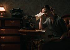 Verstoorde vrouw met brief in retro binnenland stock fotografie
