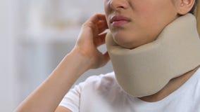Verstoorde vrouw in sprekende telefoon van de schuim de cervicale kraag, die halspijn, trauma voelen stock videobeelden