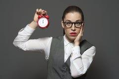 Verstoorde vrouwelijke beambte die rode klok houden royalty-vrije stock afbeelding