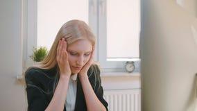 Verstoorde vrouwenzitting op het werk Blond droevig wijfje in elegante kleren die hoofd na mislukking of het slechte nieuws zitte stock video