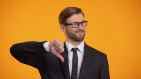 Verstoorde zakenman die duimen tonen neer, nutteloze investering, werkloosheid stock footage