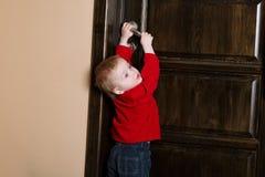 Versuche des kleinen Jungen zur offenen Tür Stockfotografie