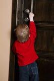 Versuche des kleinen Jungen zur offenen Tür Stockbilder