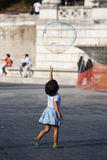 Versuche des kleinen Mädchens, zum des Seifenblasefliegens zu erreichen Stockfoto