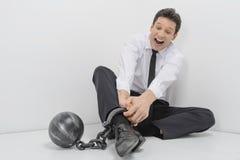 Versuchen, Freiheit zu erhalten. Entsetzter Geschäftsmann, der auf dem Boden sitzt Lizenzfreie Stockfotografie
