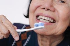 Versuchende Gebrauchszahnbürste der asiatischen älteren Frau lizenzfreies stockfoto