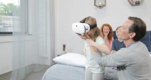 Versuchende Gläser der virtuellen Realität der Tochter mit Vater im Schlafzimmer, Familienmorgen zusammen zu Hause stock video