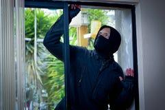 Versuchender Bruch des Einbrechers das Fenster, zum des Hauses zu betreten Stockbild