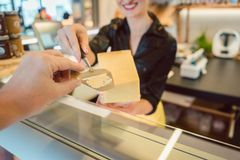 Versuchendes Stückchen des Kunden des Käses am Feinkostgeschäft entgegengesetzt stockbild
