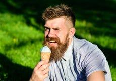 Versuchungskonzept Bärtige Manneistüte Mann mit langem Bart isst Eiscreme, während auf Gras sitzt Mann mit Bart Lizenzfreies Stockfoto