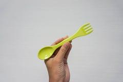 Vert de prise de femme deux-dans-un la cuillère et la fourchette Photo stock