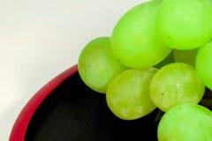 Vert Muscat du ` s du Japon placé sur des articles rouges de laque Photo stock