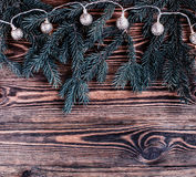 Vertakt de Kerstmis vierkante samenstelling zich met uitstekende slinger en blauwe spar op houten achtergrond koordlichten Stock Foto