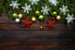 Vertakt de nieuwjaar` s groene, gele en zilveren ballen zich samen met rode sterren en met levende spar op een houten achtergrond Royalty-vrije Stock Afbeeldingen