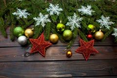 Vertakt de nieuwjaar` s groene, gele en zilveren ballen zich samen met rode sterren en met levende spar op een houten achtergrond Stock Afbeelding