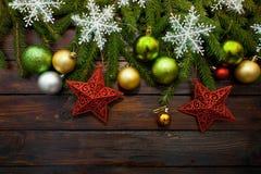 Vertakt de nieuwjaar` s groene, gele en zilveren ballen zich samen met rode sterren en met levende spar op een houten achtergrond Stock Afbeeldingen