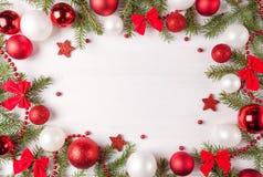 Vertakt het Kerstmis lichte kader zich dat met rode en witte snuisterijen, bogen en spar wordt verfraaid Exemplaarruimte in centr Stock Foto