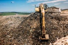 vertederos inútiles de la ciudad con los camiones del cargamento del excavador Fotos de archivo libres de regalías