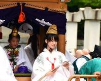 Verteilende Glücksbringer der jungen shintoistischen Priesterin während Aoba-Festivals Stockfotografie