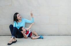 Vertelt de close-up Aziatische moeder die haar vinger richt en haar zoon om ruimte op de marmeren geweven achtergrond van de stee royalty-vrije stock afbeelding