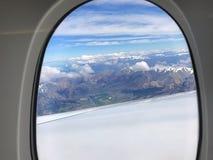 A vertente da janela dos aviões com pico de montanha ajardina Imagem de Stock