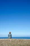 Verticaal beeld van vrouwenzitting door een kust met duidelijk blauw en c Royalty-vrije Stock Afbeeldingen