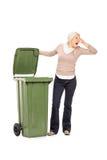 Verticaal die van een vrouw wordt geschoten die een stinky vuilnisbak opent Royalty-vrije Stock Afbeeldingen