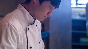 Verticaal dolly schot van jonge geconcentreerde chef-kok stock video
