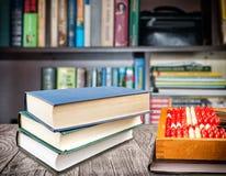Verticaal gestapelde boeken en rekeningen met een notitieboekje op het bureau Het concept van het onderwijs royalty-vrije stock afbeelding