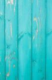 Verticaal gevestigde gekleurde verontruste turkooise verfraad, oude omheining Stock Foto's
