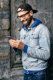 Verticaal portret van hipsterkerel in denimoverhemd, GLB en eyewear holdings moderne telefoon in zijn handen die blije uitdrukkin royalty-vrije stock afbeelding