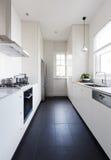 Verticaal van een lange zwart-wit keuken van de kombuisstijl Stock Afbeeldingen
