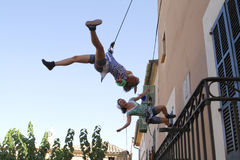 Vertical acrobats during show. Vertical acrobats holding from a rope in the walls of a building perform during a local Street theatre festival in the Spanish Royalty Free Stock Image