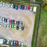 Vertical aerial photo of a gravel parking lot with rows of parked cars. stock photo