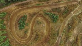 Vertical aerial shot of a motocross training track. With two motorbikes driving slowly stock video